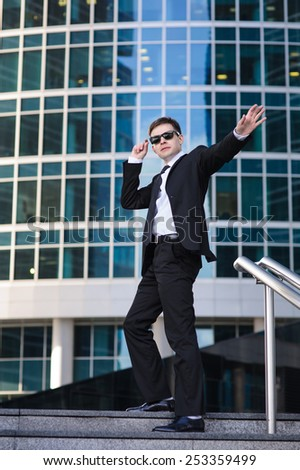 Satisfied businessman waving his hand, standing on a ladder. - stock photo