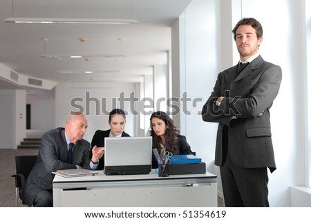 Satisfied businessman with other business people at a desk on the background - stock photo