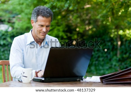 Satisfied businessman working on laptop with internet wireless - stock photo