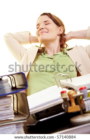 Satisfied businesswoman at her desk leaning back - stock photo