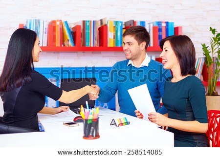 satisfied clients, couple after successful business negotiations in office - stock photo