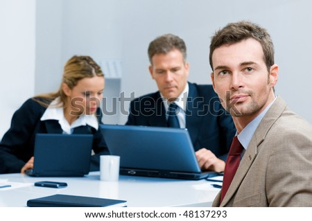 Satisfied confident businessman looking at camera with colleagues in the office - stock photo