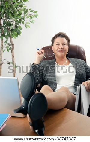 Satisfied, confident mature businesswoman with feet up on desk. - stock photo