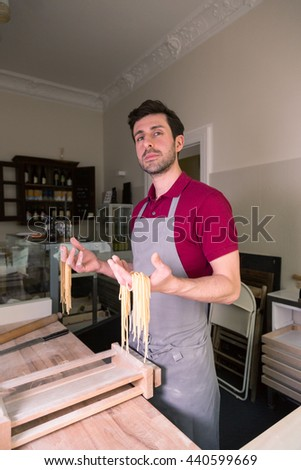 Satisfied cook showing handmade spaghetti pasta