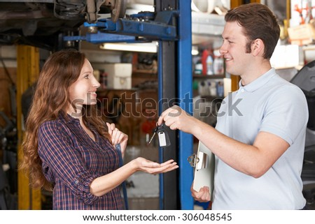 Satisfied Customer Collecting Car From Garage Mechanic - stock photo