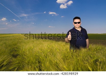 Satisfied farmer in the wheat field on sany day