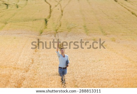 Satisfied farmer with laptop and raised arm high in the air standing in ripe wheat field - stock photo