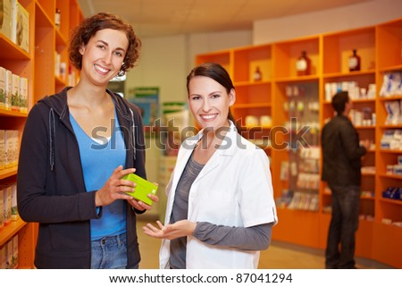 Satisfied female customer with pharmacist in a pharmacy - stock photo