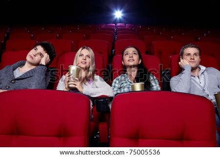 Satisfied girls and bored boys watching a movie at the cinema - stock photo