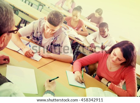 Satisfied girls and boys taking the notes while teacher giving a class