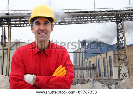 Satisfied industrial worker in a factory - stock photo