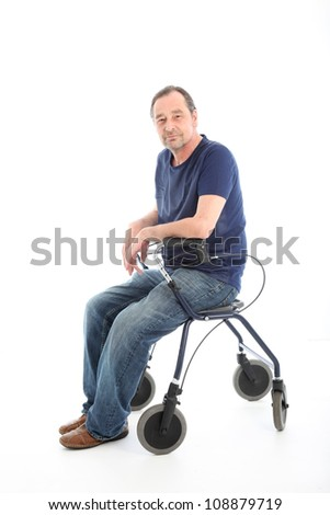 Satisfied man resting on a health walker Satisfied middle-aged man resting onthe seat of a health walker which he is using to aid mobility as a result of a disability or injury