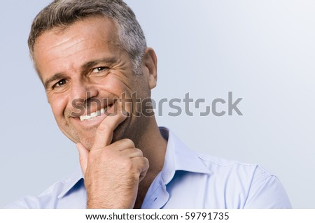 Satisfied mature businessman smiling and looking at camera - stock photo