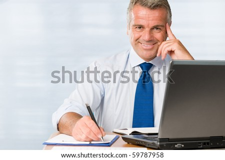 Satisfied mature businessman smiling in his modern office at work - stock photo