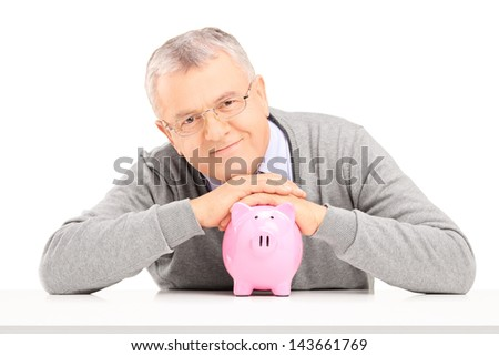 Satisfied mature gentleman posing over a piggy bank isolated on white background