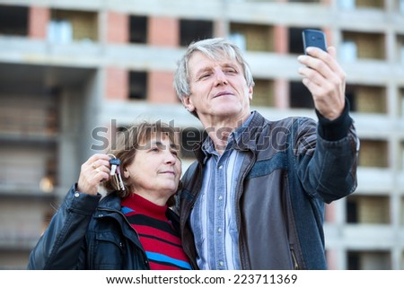 Satisfied mature husband and wife making picture with house key in hand - stock photo