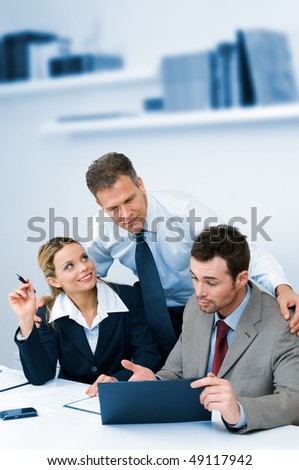 Satisfied mature manager supervising and collaborate with his business team in modern office - stock photo
