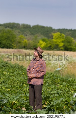 Satisfied old man farmer resting in field after hard work - stock photo