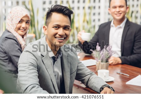 Satisfied proud business team looking at camera and smiling - stock photo