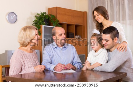 Satisfied relatives sitting at the table and discussing finances - stock photo