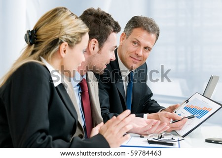Satisfied senior businessman showing growing chart at his happy colleagues in office - stock photo
