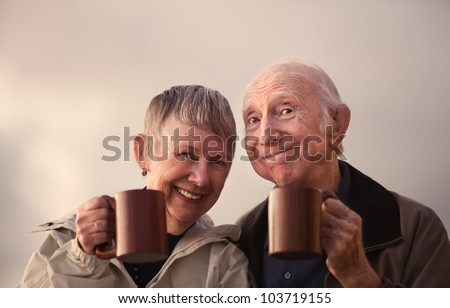 Satisfied senior citizen couple outdoors with coffee mugs - stock photo
