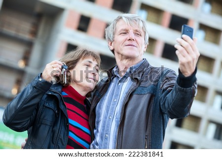 Satisfied senior couple with house keys making selfie together - stock photo