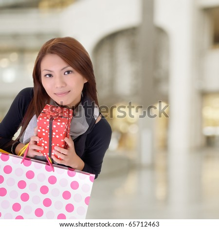 Satisfied shopping woman holding bags in department store. - stock photo