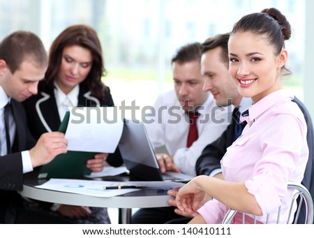 Satisfied smiling business woman looking at camera with working colleagues in office - stock photo