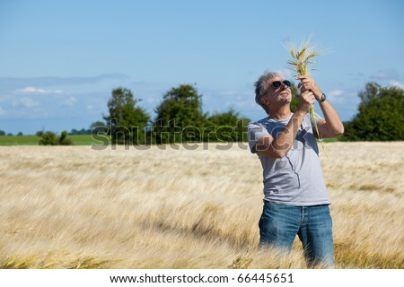 Satisfied  smiling farmer in his field. - stock photo