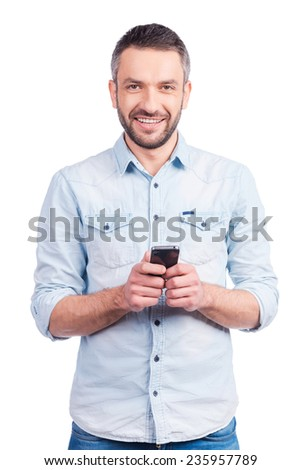 Satisfied with his brand new smart phone. Happy young man in casual wear holding smart phone and smiling while standing isolated on white background - stock photo