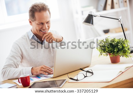Satisfied with his work. Cheerful mature man working on laptop and smiling while sitting at his working place - stock photo