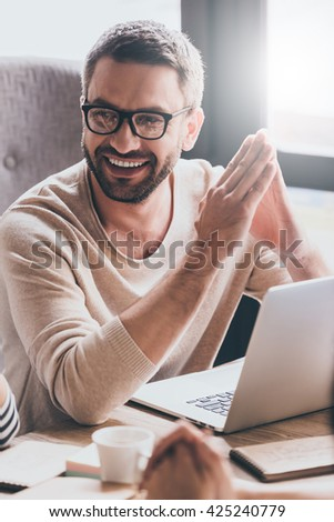 Satisfied with his work. Close-up part of handsome young man discussing something with his coworkers with smile while sitting at the office table  - stock photo