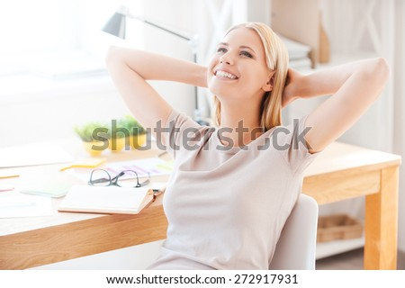 Satisfied with the work done. Beautiful young woman holding hands behind head and smiling while sitting at her working place in office  - stock photo