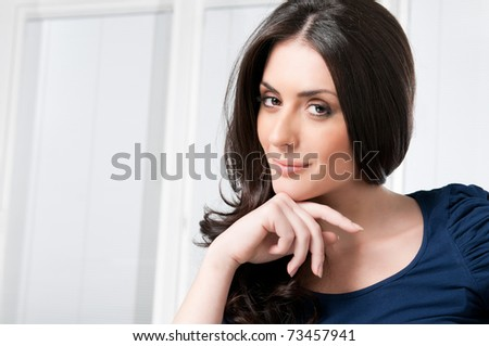 Satisfied young beautiful woman looking at camera at home - stock photo