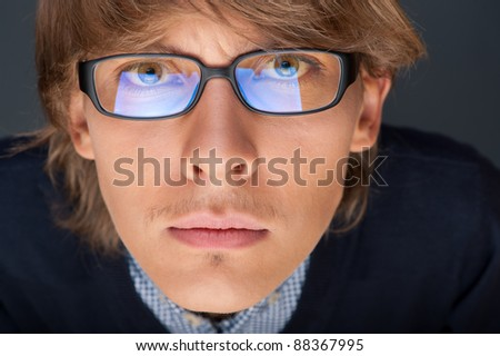 Satisfied young man with glasses looking at camera like at laptop screen, which reflects at glasses - stock photo