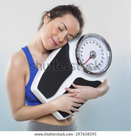 satisfied young woman in love with her weight scale