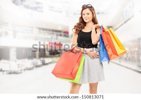 Satisfied young woman posing with shopping bags in a shopping center - stock photo