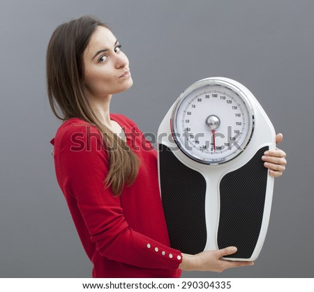 satisfied young woman with weighting scale in hands for concept of weight loss or weight control - stock photo