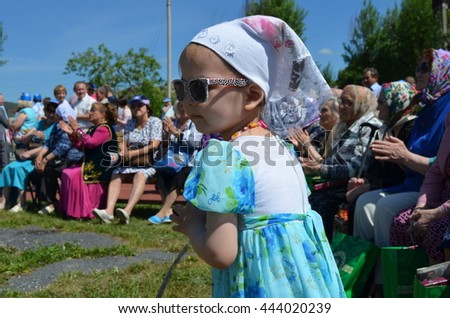 Satka, Chelyabinsk region, Russia - June 19, 2016: Little girl in sunglasses looks festive presentation. Sabantuy (Sabantui ) is a traditional celebration of the end of spring field work.