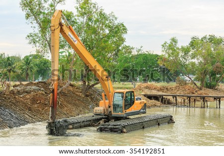 SATTAHIP CHONBURI - DEC,22 : The dirty backhoe working in mud lake for take the mud dam beside the pool site where is renovated new landscape in golf course . THAILAND DEC,22 2015 - stock photo