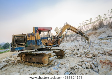 SATTAHIP CHONBURI - MARCH,4 : The old industrial backhoe, bulldozer moving drilling for road construction site that parking for rest after work day in twilight time. THAILAND MARCH,4 2016