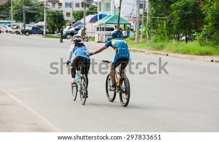 "SATTAHIP,THAILAND - JULY 19 : Two of  cyclist are pedaling inside Sattahip Naval base area in ""Tour of Sattahip 15"" tournament racing in range 50,100 Kms. on July 19,2015"