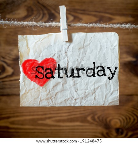 Saturday on red heart on aged paper hanging on the clothesline. On old wood background - stock photo