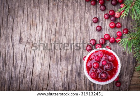 sauce of wild organic cranberries on a wooden table with berries and pine branches on a live cut down a tree - stock photo
