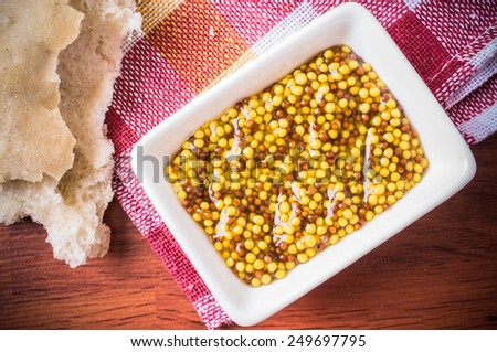 Sauce with mustard seeds and vinegar. Appetizer with bread, tapas - stock photo