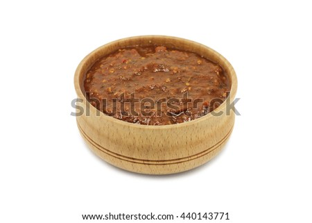 sauce with spices and herbs in a wooden dish on a white background - stock photo