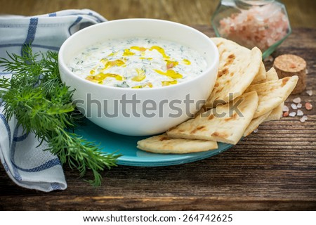 Sauce with yogurt and cucumber for starter with slices of bread on a white plate and a dark natural wood background. selective Focus