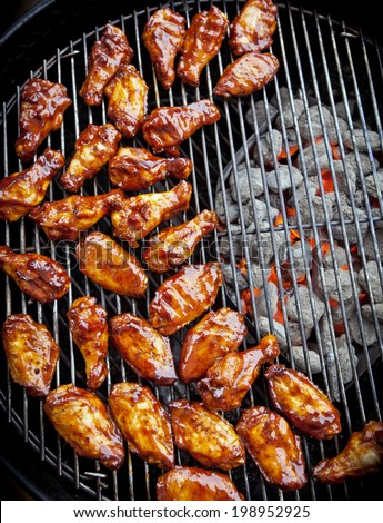 Sauced BBQ chicken wings over hot coals - stock photo