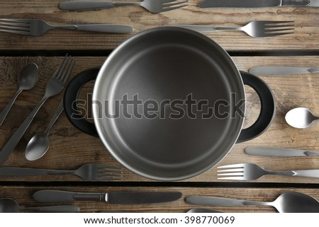Saucepan and silver cutlery on wooden table, top view - stock photo